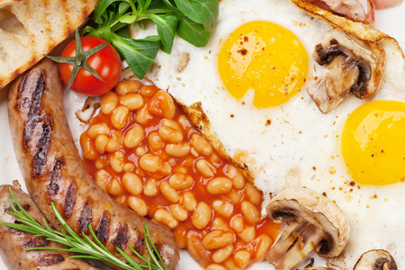 English breakfast. Fried eggs, sausages, bacon, beans, tomatoes Standard-Bild - 102310286