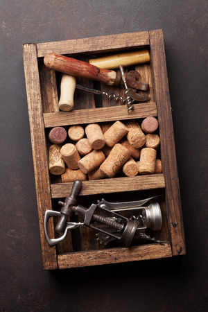 Wine corkscrews and corks in wooden box. Top view