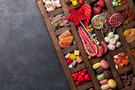 Colorful sweets box. Lollipops, macaroons, marshmallow, marmalade and candies. Top view with space for your greetings Stok Fotoğraf
