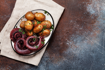 Grilled octopus with small potatoes with herbs and spices. Top view with space for your text Stock Photo