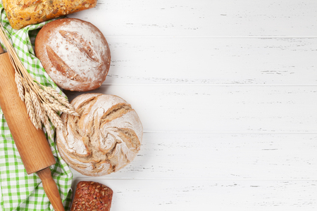 Various crusty bread on white wooden background. Top view with space for your text