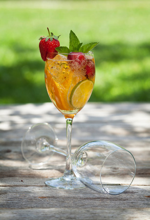 Homemade lemonade or sangria with summer fruits and berries. Outdoor.