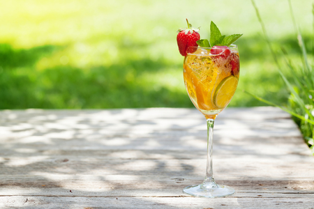 Homemade lemonade or sangria with summer fruits and berries. Outdoor. With space for your text
