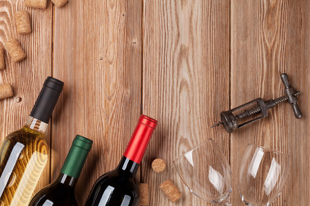 Wine bottles on wooden table. Red and white wine. Top view with space for your text
