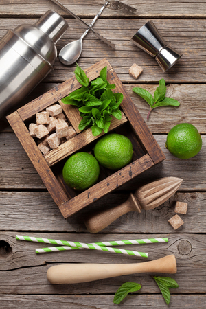 Mojito cocktail ingredients and bar accessories box on wooden table. Top view