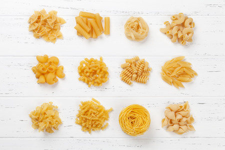 Various pasta on white wooden table. Cooking concept. Top view