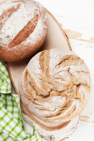 Homemade crusty bread on white wooden table. Top view Stockfoto - 103365126