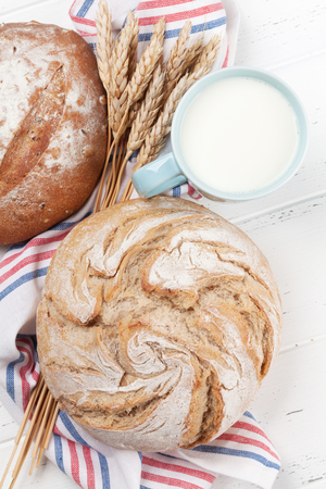 Homemade crusty bread and milk on wooden table. Top view Stockfoto