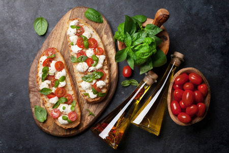 Caprese bruschetta toasts with cherry tomatoes, mozzarella and basil. Top view Banque d'images - 103675068