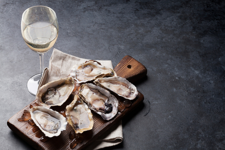 Opened oysters, ice on board and white wine on stone table. With copy space