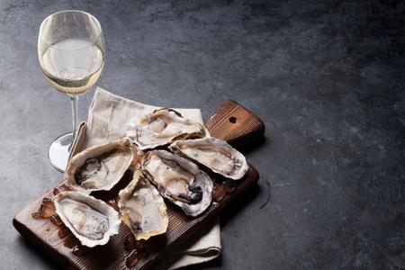 Huîtres ouvertes, glace à bord et vin blanc sur table en pierre. Avec copie espace