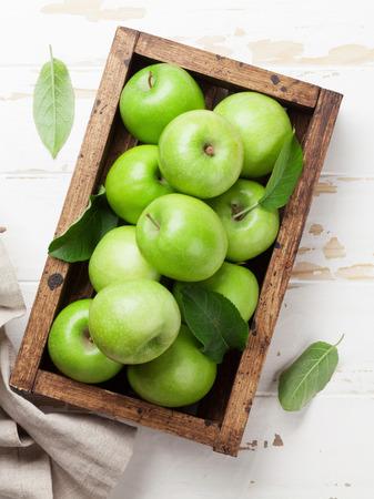 Rijpe groene appels in houten doos. Bovenaanzicht