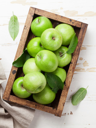 Ripe green apples in wooden box. Top view