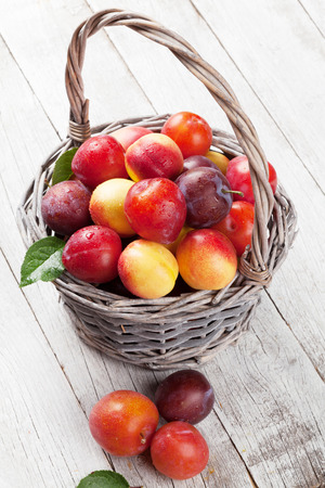 Fresh ripe peaches and plums in basket on wooden table 写真素材