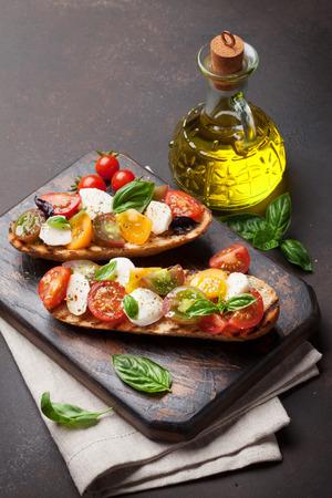 Bruschetta with cherry tomatoes, mozzarella and basil on wooden board. Caprese salad
