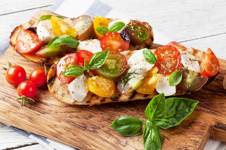 Bruschetta with cherry tomatoes, mozzarella and basil on wooden board. Caprese salad Banque d'images - 103987397