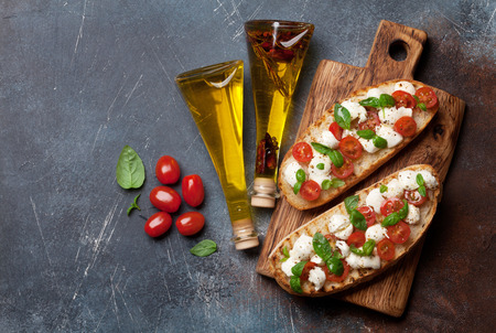Caprese bruschetta toasts with cherry tomatoes, mozzarella and basil. Top view with space for your text Banque d'images - 104364125