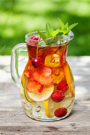 Homemade lemonade or sangria with summer fruits and berries. Outdoor