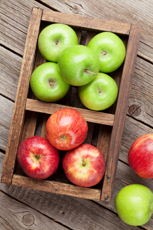 Ripe green and red apples on wooden table. Top view