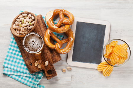 Lager beer and snacks on wooden table. Nuts, chips, pretzel. Top view with chalkboard for copy space Stock Photo