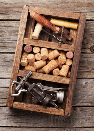 Wine accessories. Corkscrew and corks in wooden box. Top view
