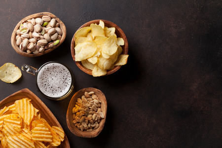 Lager beer and snacks on stone table. Nuts, chips. Top view with copyspace Stock Photo