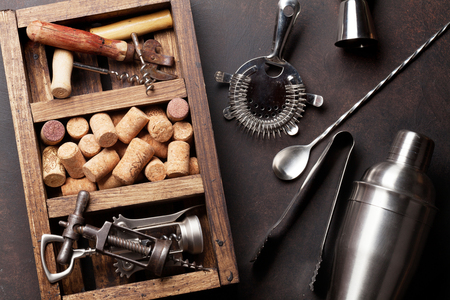 Wine and cocktail accessories. Corkscrew and corks in wooden box. Top view