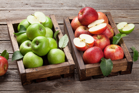 Ripe green and red apples boxes on wooden table