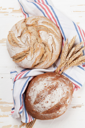 Various crusty bread on white wooden table. Top view Stockfoto - 105783259