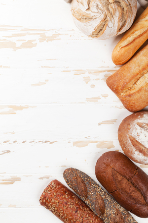 Various crusty bread and buns on white wooden table. Top view with space for your text