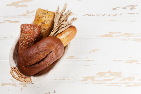 Various crusty bread and buns on white wooden table. Top view with space for your text Stockfoto