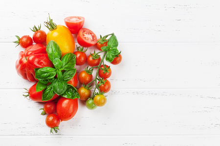 Fresh garden tomatoes and basil on cooking table. Top view with space for your recipe 写真素材 - 106492443