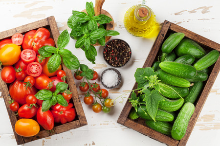 Fresh garden tomatoes and cucumbers on cooking table. Top view Archivio Fotografico