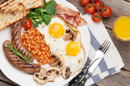 English breakfast. Fried eggs, sausages, bacon, beans, toasts, tomatoes, orange juice on wooden table. Top view Stock Photo