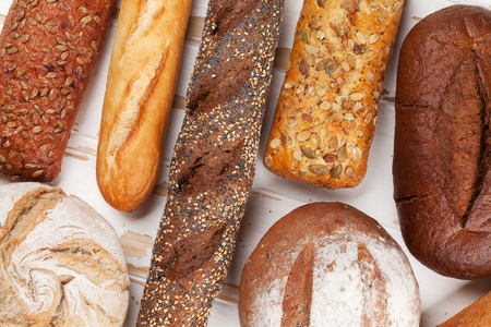 Various crusty bread and buns on white wooden table. Top view