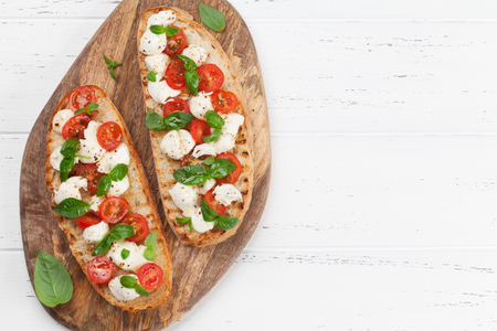Caprese bruschetta toasts with cherry tomatoes, mozzarella and basil. Top view with space for your text Banque d'images - 107355426