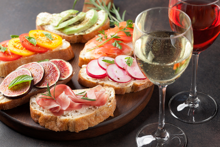 Rose and white wine with brushetta or traditional spanish tapas. Appetizers italian antipasti snacks set on wooden board Stok Fotoğraf