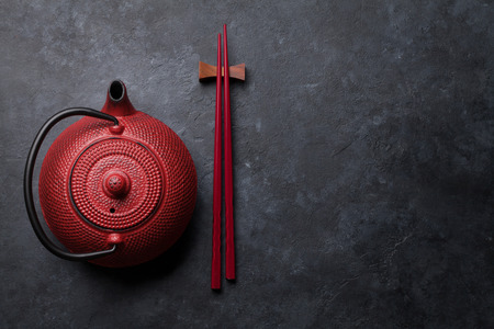 Red tea pot and sushi chopsticks. Top view with space for your text. Flat lay