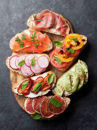 Brushetta or traditional spanish tapas. Appetizers italian antipasti snacks set on wooden board. Top view and flat lay Фото со стока