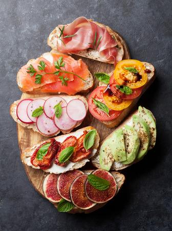 Brushetta or traditional spanish tapas. Appetizers italian antipasti snacks set on wooden board. Top view and flat lay Reklamní fotografie - 107495900