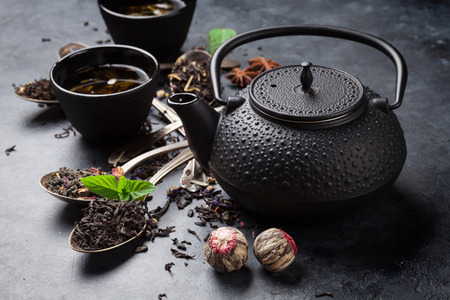 Various tea in spoons and teapot. Black, green and red tea