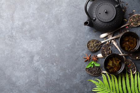 Various tea in spoons and teapot. Black, green and red tea. Top view with space for your text