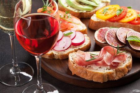 Brushetta or traditional spanish tapas. Appetizers italian antipasti snacks set on wooden board with rose and white wine