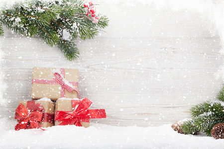 Christmas gift boxes and fir tree branch covered by snow in front of wooden wall. View with copy space