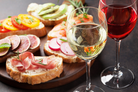 Rose and white wine with Brushetta or traditional spanish tapas. Appetizers italian antipasti snacks set on wooden board Foto de archivo - 108185243