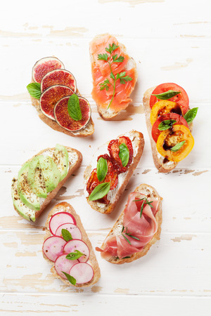 Brushetta or traditional spanish tapas. Appetizers italian antipasti snacks set on wooden board. Top view and flat lay Stock Photo