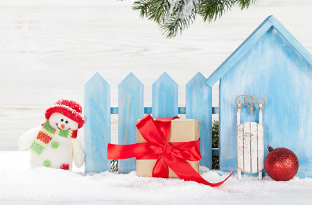 Christmas snowman, sledge toys, gift box and fir tree branch. Xmas backdrop with copy space