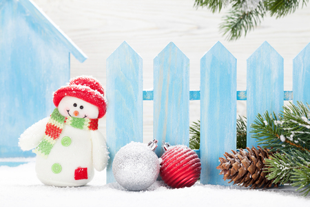 Christmas snowman toys, baubles and fir tree branch. Фото со стока