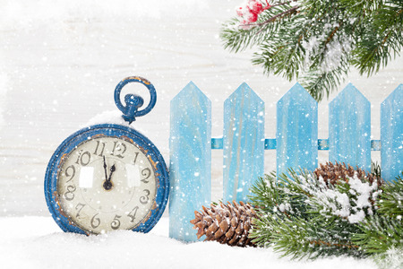 Christmas alarm clock and fir tree branch covered by snow in front of wooden wall Фото со стока