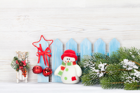 Christmas snowman, sledge toys and fir tree branch. Xmas backdrop with copy space